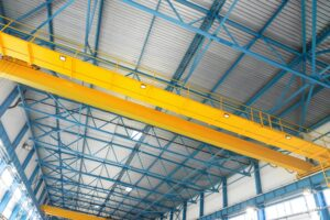 Blue steel frame of metal industrial roof in warehouse with yellow cranes under the ceiling