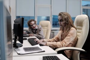 Young spooky zombie businesswoman sitting by desk in front of computer monitor and networking